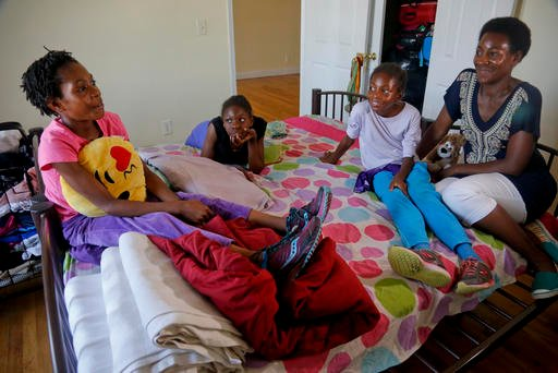 In this Wednesday, July 20, 2016 photo, Tonia Handy, far right, and her daughters, Rainn Sheppard, 10, far left, Tai Sheppard, 11, second from left, and Brooke Sheppard, 8, second from right, together in the bedroom of their apartment.