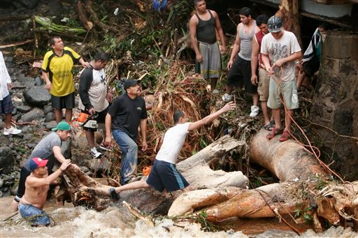 Residents try to pull a tree trunk from El Jute river to prevent it from damaging a bridge in La Libertad, south El Salvador , Sunday, May 30 ,2010.