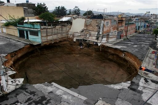A sinkhole created by tropical storm Agatha covers a street intersection in dowtown of Guatemala City on Sunday, May 30, 2010. (AP Photo/STR)