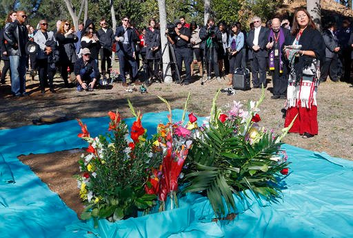 Raquel Salinas, right, gives a Native American sage blessing during burial services for the unclaimed remains of 1,430 people at Evergreen Cemetery in Los Angeles, Wednesday, Nov. 30, 2016.