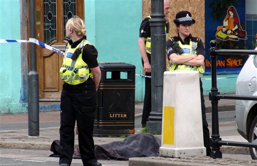 Police stand next to a body following a shooting on Duke Street, in the town of Whitehaven in northwest England Wednesday June 2, 2010. (AP Photo/Rod Minchin/PA Wire)