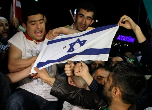 Friends and family members of Turkish activists who were deported by Israel two days after a deadly naval raid by Israeli forces in the Mediterranean Sea, set on fire an Israeli flag June 3. (AP Photo/Ibrahim Usta)