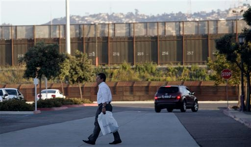 A man leaves an upscale shopping mall in front of metal barricades marking the border with Tijuana, Mexico, Wednesday, June 2, 2010 in San Diego.