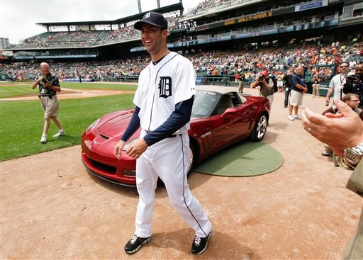 Detroit Tigers pitcher Armando Galarraga smiles while beings presented a Chevrolet Corvette by the manufacturer on the field before a baseball game against the Cleveland Indians in Detroit.