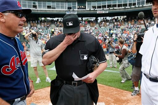 Home plate umpire Jim Joyce wipes tears during the exchange of lineup cards between Cleveland Indians bench coach Tim Tolman, left, and Detroit Tigers pitcher Armando Galarraga.