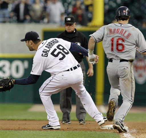 Detroit Tigers pitcher Armando Galarraga (58) covers first base as Cleveland Indians' Jason Donald, right, runs to the base and umpire Jim Joyce looks on in the ninth inning of a baseball game in Detroit Wednesday, June 2, 2010.