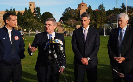 n this Feb. 1, 2016, file photo, International Olympic Committee President Thomas Bach, second from left, is flaked by Los Angeles Mayor Eric Garcetti, left, and LA 2024 chairman Casey Wasserman, second from right.