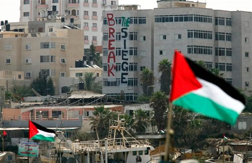 Backdropped by a banner on a building, Palestinian flags are seen atop fishing boats belonging to Palestinians at the port in Gaza City.