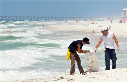 A crew picks up oil that washed up along Pensacola Beach, Fla., Friday, June 4, 2010. Waves of gooey tar blobs were washing ashore in growing numbers on the white sand of the Florida Panhandle Friday as a slick from the BP spill drifted closer to shore. (