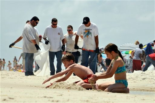 Michael Tabb, 10, and his sister Kathleen Tabb, 8, of Meridian, Miss., play in the sand as crews clean up tar along Pensacola Beach, Fla.