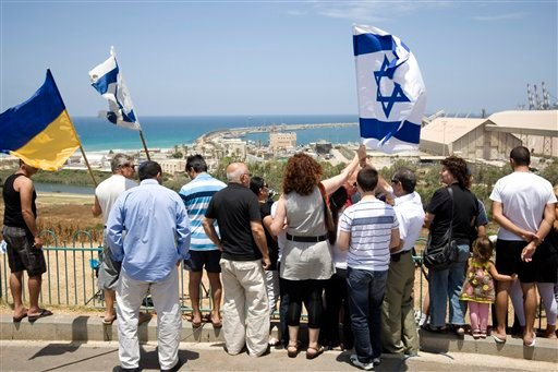 Israelis wave flags as a military naval ship, not seen, sails in the port of Ashdod, Israel, Saturday, June 5, 2010. (AP Photo/Ariel Schalit)