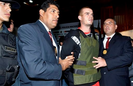 Police officers escort Joran Van der Sloot, second right, during a press conference at a police station in Lima, Saturday, June 5, 2010.