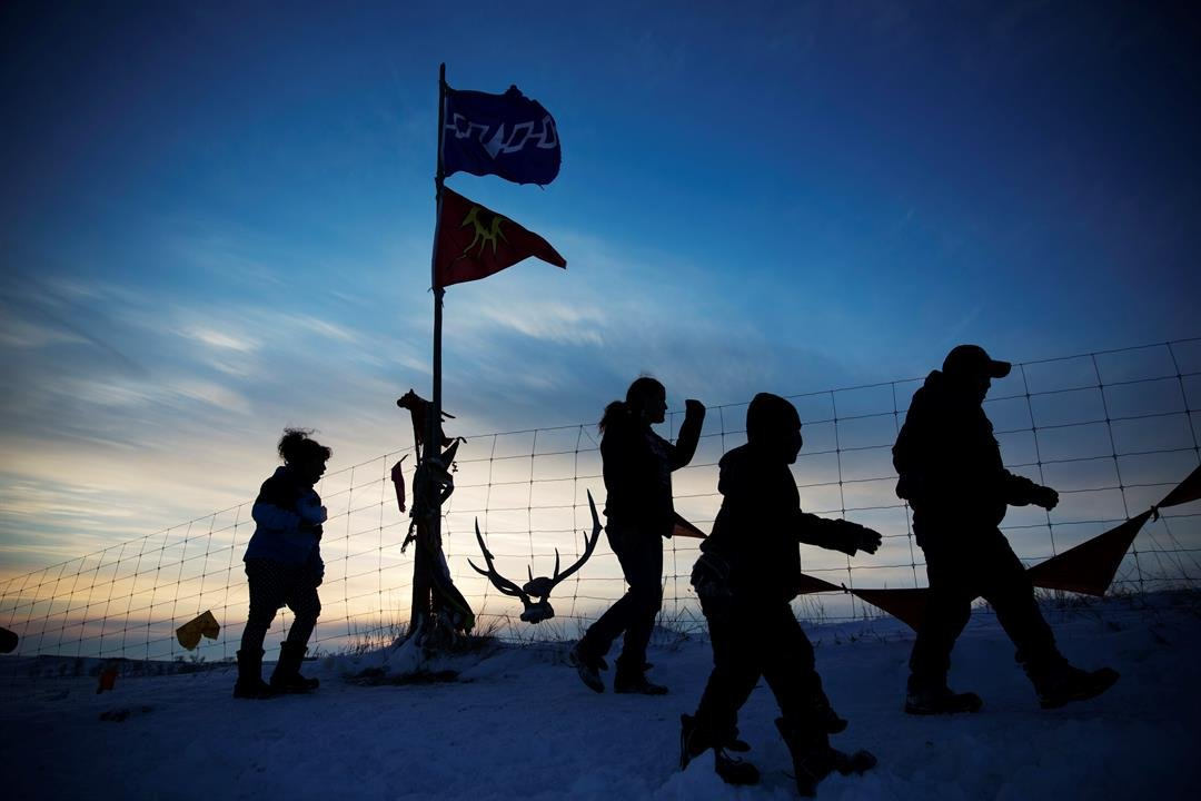 A Native American tribal flag stands atop a hill overlooking the Oceti Sakowin camp where people have gathered to protest the Dakota Access oil pipeline in Cannon Ball, N.D., Saturday, Dec. 3, 2016. (AP Photo/David Goldman)