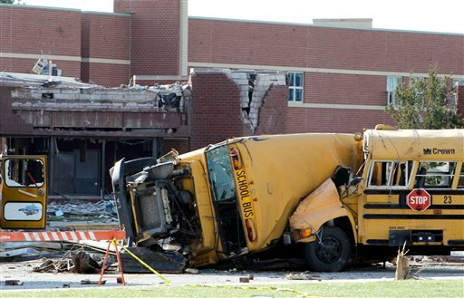 School buses are shown after being tossed by a tornado in the parking lot of damaged Lake High School in Lake Township, Ohio Sunday, June 6, 2010.