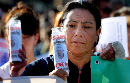 A woman holds a candle covered by a picture of late Mexican Anastasio Hernandez during a protest at the San Ysidro border crossing that separates Tijuana from San Diego, in Tijuana, Mexico.
