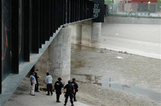 Mexican federal police and forensic experts stand next to the body of 14 year-old Sergio Adrian Hernandez Huereca, under the Paso Del Norte border bridge, as US officials watch from the US side at right, in Ciudad Juarez, northern Mexico, Monday, June 7,