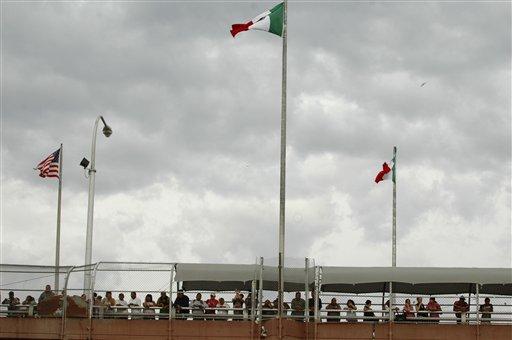 People standing on the Paso Del Norte border bridge watch the police activity below after 14 year-old Sergio Adrian Hernandez Huereca was killed below the bridge.