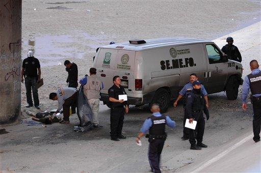 Mexican forensic experts examine the body of 14 year-old Sergio Adrian Hernandez Huereca under the Paso Del Norte border bridge.
