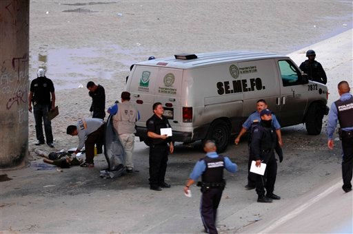 Mexican forensic experts examine the body of 14 year-old Sergio Adrian Hernandez Huereca under the Paso Del Norte border bridge.