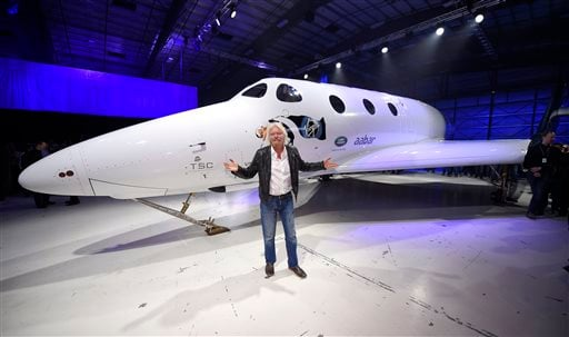 Sir Richard Branson poses in front of Virgin Galactic's SpaceShipTwo space tourism rocket after it was unveiled, Friday, Feb. 19, 2016, in Mojave, Calif.