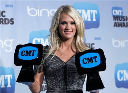 Country singer Carrie Underwood poses with her Video of the Year award and CMT Performance of the Year award in the press room at the 2010 CMT Music Awards, in Nashville, Tenn. on Wednesday, June 9, 2010. (AP Photo/Peter Kramer)