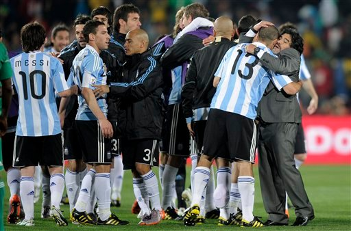 Argentina head coach Diego Maradona, right, hugs Argentina's Walter Samuel, second from right, as the team celebrate their victory. (AP Photo/Martin Meissner)