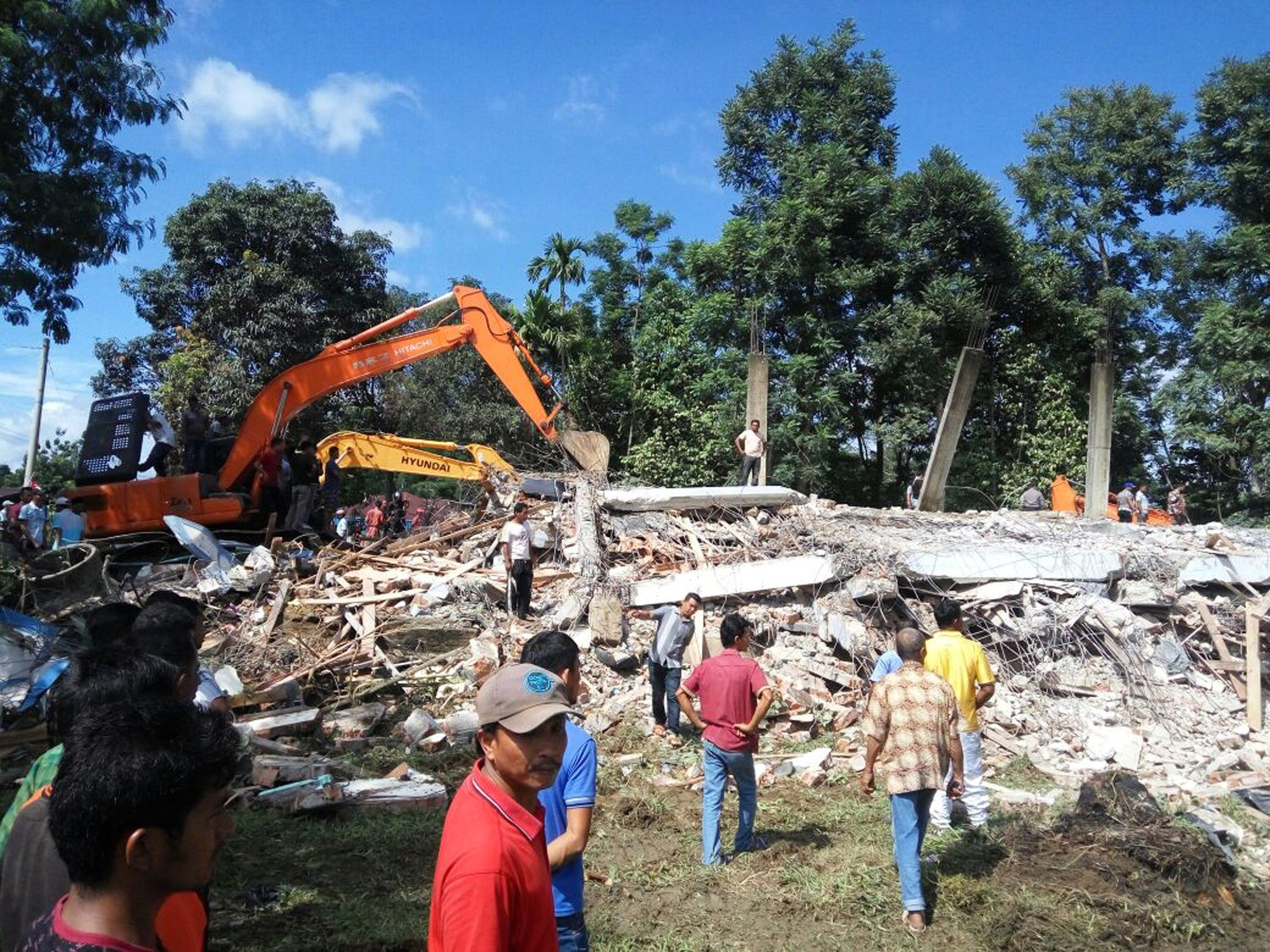 Rescuers use heavy machine to search for survivors under the rubble of a collapsed building after an earthquake in Pidie Jaya, Aceh province, Indonesia, Wednesday, Dec. 7, 2016.