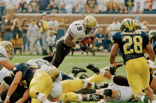 In this Sept. 24, 1994, file photo, Colorado's Rashaan Salaam (19) dives over the goal line for a 1-yard touchdown against Michigan in the first quarter of an NCAA college football game, in Ann Arbor, Mich.
