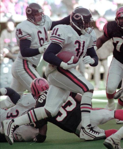 In this Dec. 10, 1995, file photo, Chicago Bears running back Rashaan Salaam breaks through the line against the Cincinnati Bengals during an NFL game in Cincinnati.