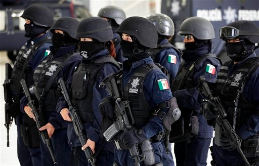 Police officers stand in formation during a presentation of drug dealing suspects to the media in Mexico City, Tuesday, June 15, 2010. (AP Photo/Eduardo Verdugo)