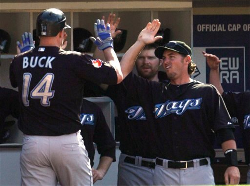 Toronto Blue Jays' John Buck is congratulated upon returning to the dugout after his two-run homer against the San Diego Padres in the fifth inning of a baseball game Wednesday, June 16, 2010, in San Diego. (AP Photo/Lenny Ignelzi)