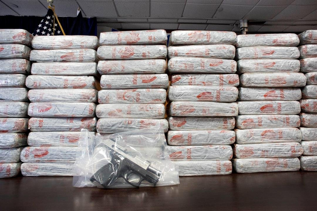 FILE - This Tuesday, May 19, 2015 file photo shows a firearm and 154 pounds of heroin worth at least $50 million displayed during a Drug Enforcement Administration news conference in New York.
