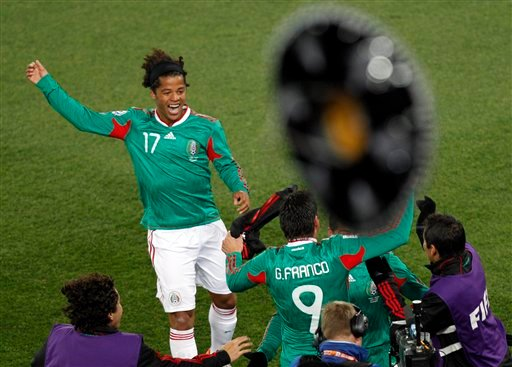 Mexico's Giovani Dos Santos and teammates celebrate as a sombrero hat is thrown in the air from the stands after Javier Hernandez scored during the World Cup group A soccer match between France and Mexico