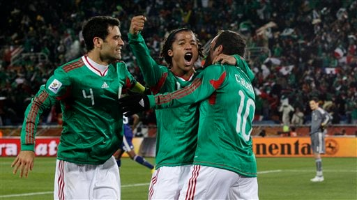 Mexico's Cuauhtemoc Blanco, right, celebrates after scoring a penalty goal with fellow team members Giovani Dos Santos, center, and Rafael Marquez, left, during the World Cup group A soccer match between France and Mexico.
