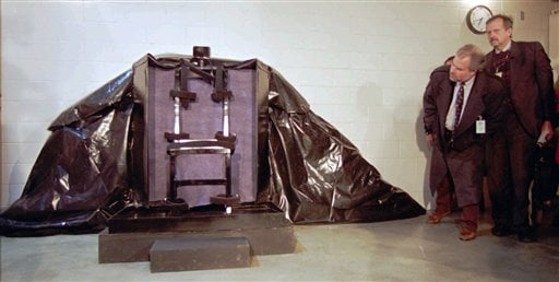 In this Jan. 24, 1996 file photo, reporters look at the chair to be used to execute John Albert Taylor by firing squad in the Utah State Prison at Point of the Mountain, Utah.