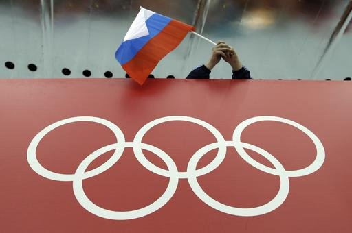 In this Feb. 18, 2014 file photo, a Russian skating fan holds the country's national flag over the Olympic rings.