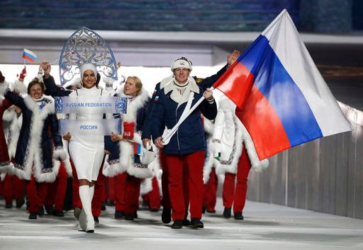 In this Feb. 7, 2014 file photo Alexander Zubkov of Russia carries the national flag as he leads the team during the opening ceremony of the 2014 Winter Olympics in Sochi, Russia.