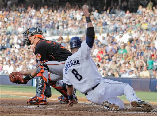 San Diego Padres' Yorvit Torrealba, right, scores ahead of the tag of Baltimore Orioles catcher Matt Wieters, left, during the first inning of a baseball game Saturday, June 19, 2010 in San Diego. (AP Photo/Denis Poroy)