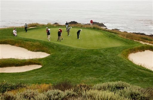 Tiger Woods, right, and Dustin Johnson, second from right, putt on the seventh green during a practice round of the U.S. Open Championship golf tournament in Pebble Beach, Calif., Monday, June 14, 2010. (AP Photo/Eric Risberg)