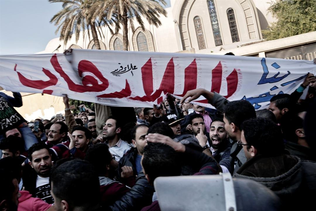 """Coptic Christians hold a banner with Arabic that reads, """"no to terrorism,"""" during a protest outside the St. Mark Cathedral in central Cairo, following a deadly bombing Dec. 11, 2016. (AP Photo/Nariman El-Mofty)"""