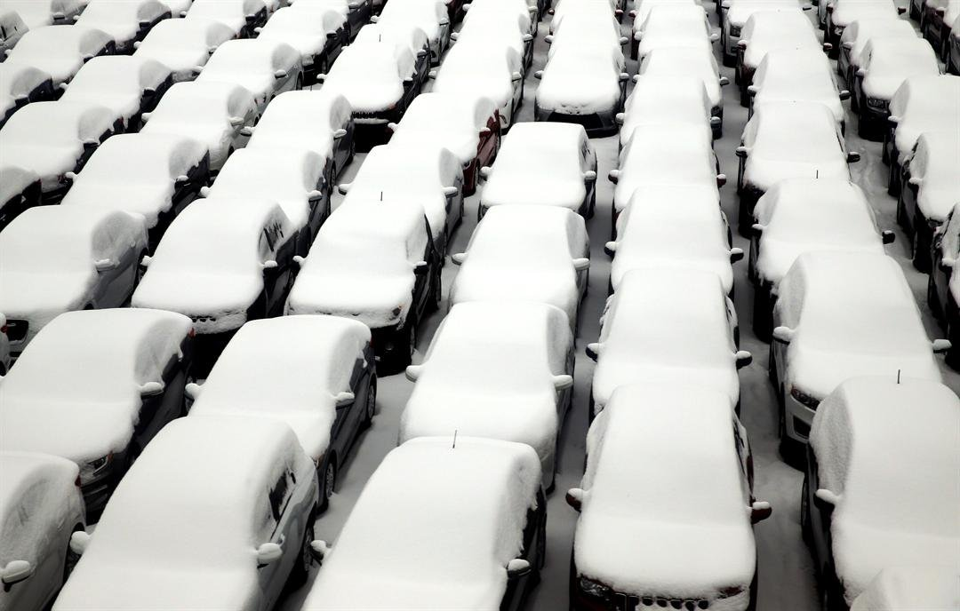 Snow covers vehicles in a rental car parking lot at O'Hare International Airport, on Sunday, Dec. 11, 2016, in Chicago. (AP Photo/Nam Y. Huh)