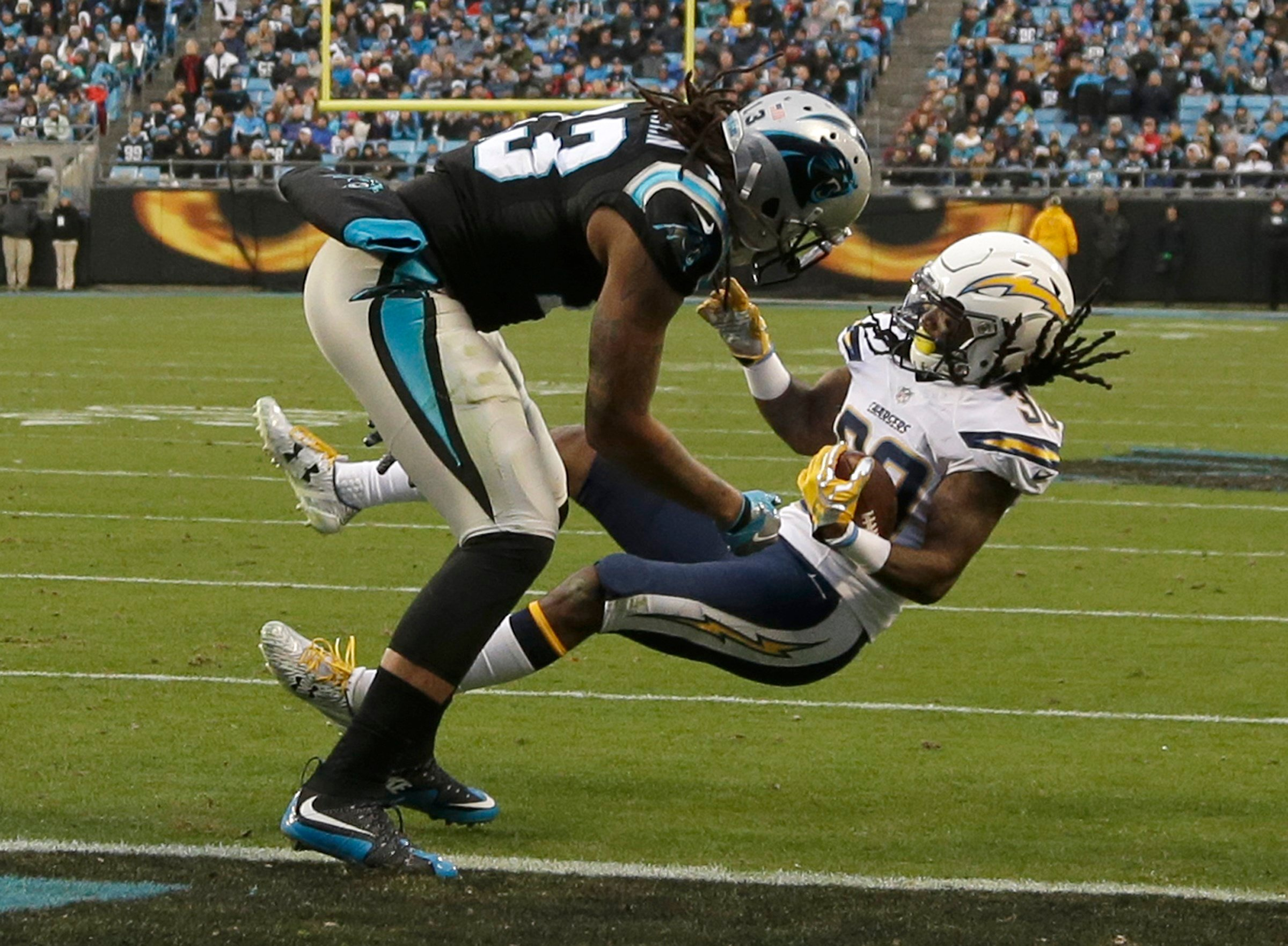 San Diego Chargers' Trovon Reed, right, intercepts a pass intended for Carolina Panthers' Kelvin Benjamin, left, in the second half of an NFL football game in Charlotte, N.C., Sunday, Dec. 11, 2016. (AP Photo/Bob Leverone)