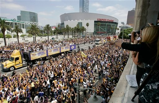 Thousands watch as the Los Angeles Lakers celebrate their NBA championship in a parade down Figueroa Street in Los Angeles Monday, June 21, 2010. (AP Photo/Reed Saxon)
