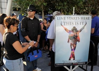 FILE - In this Sept. 24, 2009 file photo, Michael Jackson fans arrive to buy tickets for the 'Michael Jackson's This Is It' film, at L.A. Live in Los Angeles.