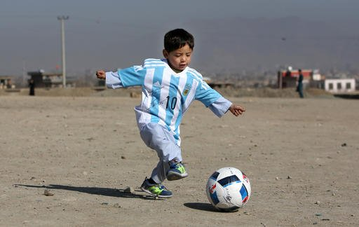 A Friday, Feb. 26, 2016 photo from files of Murtaza Ahmadi, a five-year-old Afghan Lionel Messi fan playing with a soccer ball during a photo opportunity as he wears a shirt signed by Messi, in Kabul, Afghanistan.