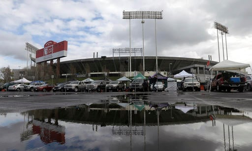 In this Dec. 24, 2015, O.co Coliseum is reflected in a puddle before an NFL football game between the Oakland Raiders and the San Diego Chargers in Oakland, Calif.
