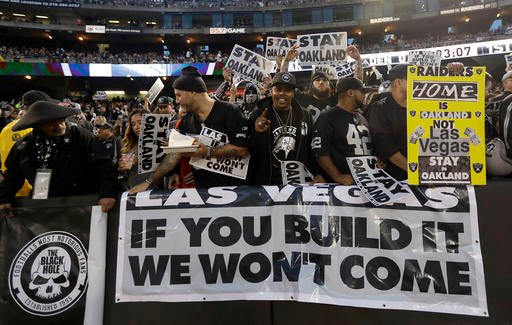In this Nov. 6, 2016, file photo, Oakland Raiders fans hold up signs about the team's possible move to Las Vegas during an NFL football game between the Raiders and the Denver Broncos in Oakland, Calif.