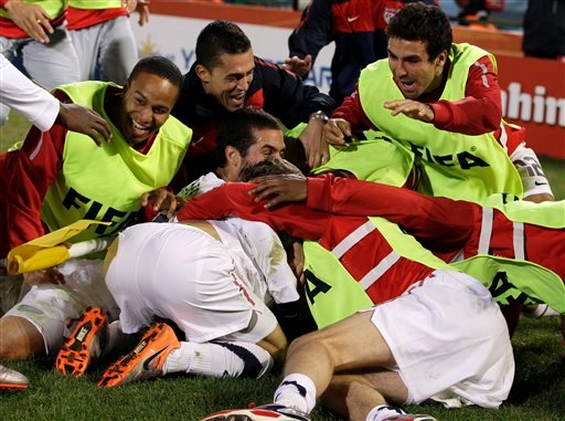 United States' Landon Donovan, hidden, celebrates with teammates after scoring a goal during the World Cup group C soccer match between the United States and Algeria at the Loftus Versfeld Stadium in Pretoria, South Africa, Wednesday, June 23, 2010.