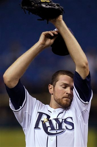 Tampa Bay Rays pitcher Wade Davis wipes his forehead as he struggles during the first inning of an interleague baseball game against the San Diego Padres Tuesday, June 22, 2010, in St. Petersburg, Fla.
