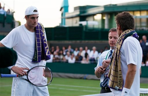 John Isner of the US, left, and Nicolas Mahut of France listen, as a tournament official calls off their men's singles, first round match because of bad light, at the All England Lawn Tennis Championships at Wimbledon, Tuesday, June 22, 2010. (AP Photo/Sa